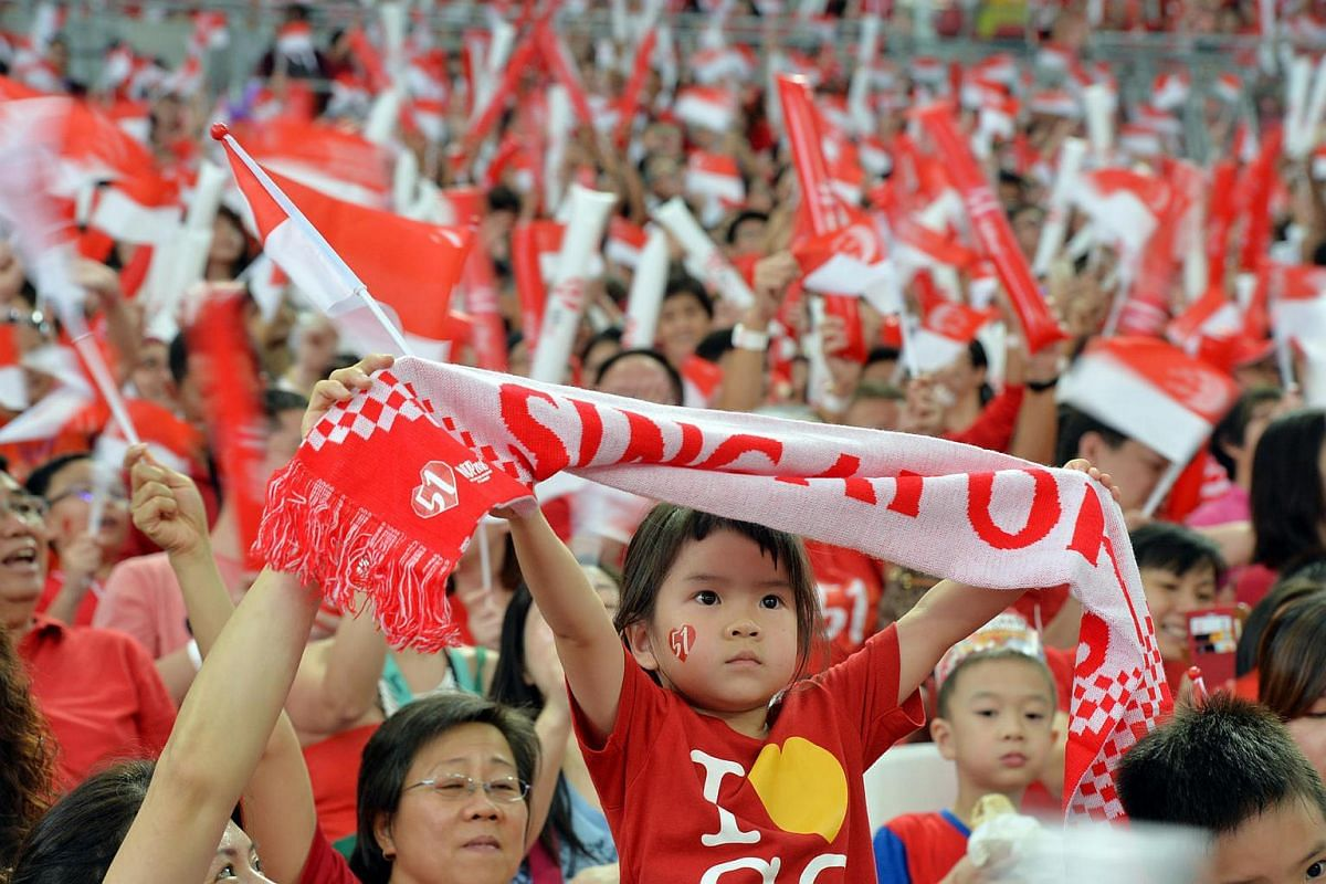A young girl in the stadium crowd holds aloft a Singapore scarf.