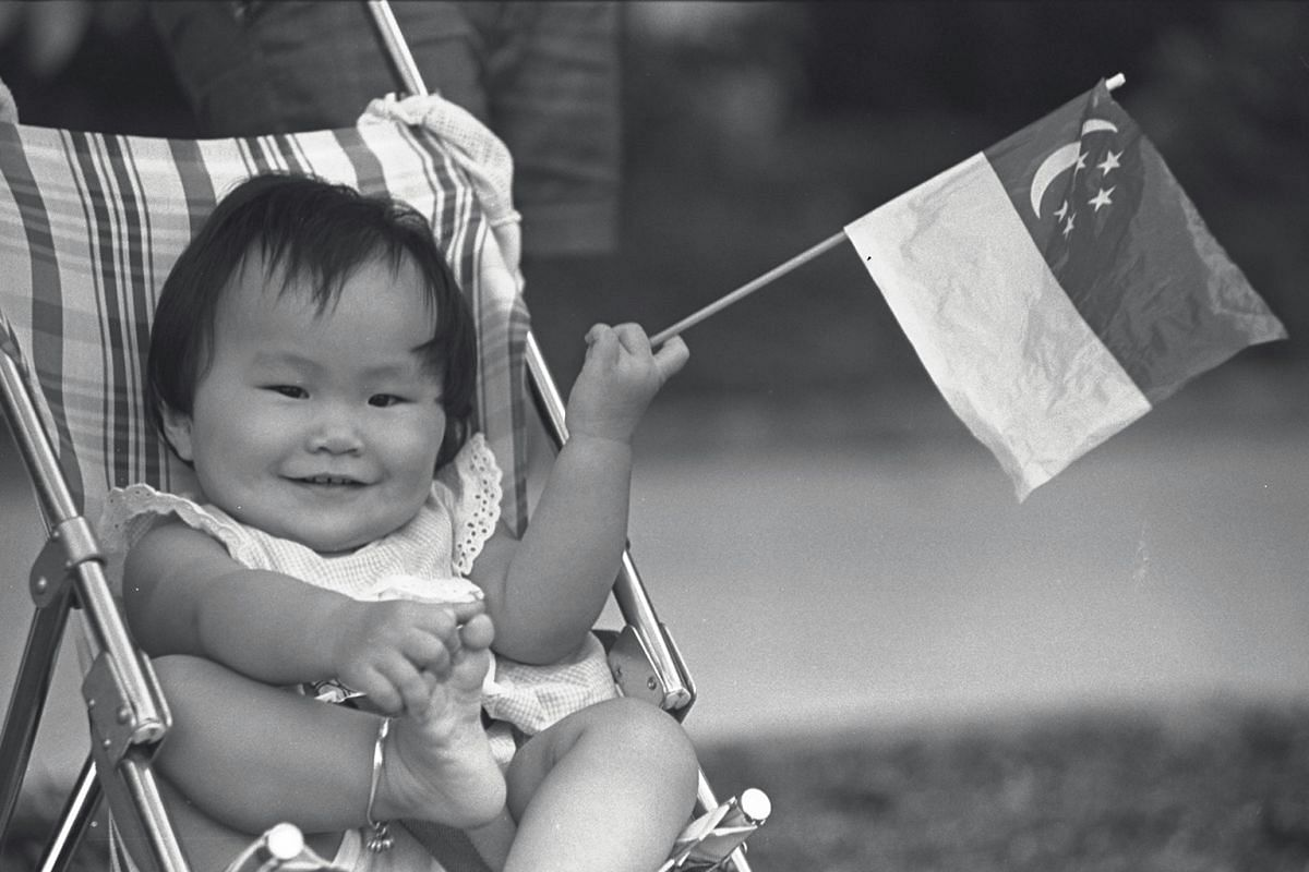 Waving a mini-flag, 10-month-old Giam Seow Hooi awaited the passage of colourful floats at the People's Association in Kallang in 1985. Her father had wheeled her all the way from their Beach Road home in her stroller to catch the procession as it