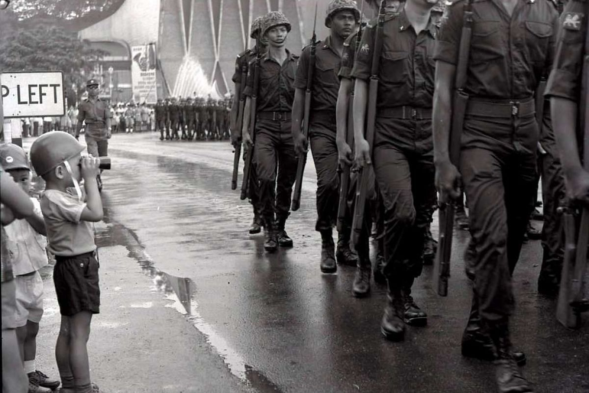 A contingent of soldiers marching through puddles in front of the National Theatre in 1968. There were 81 contingents that year. Participants marched from the Padang, past City Hall to High Street, South Bridge Road, Chinatown, Tanjong Pagar, Neil Ro