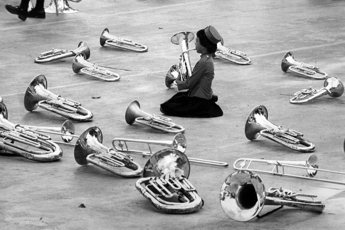 St Theresa's Convent student Christina Wong, 13, warming up as her bandmates take a break before the start of the parade at the Tiong Bahru centre in 1977.
