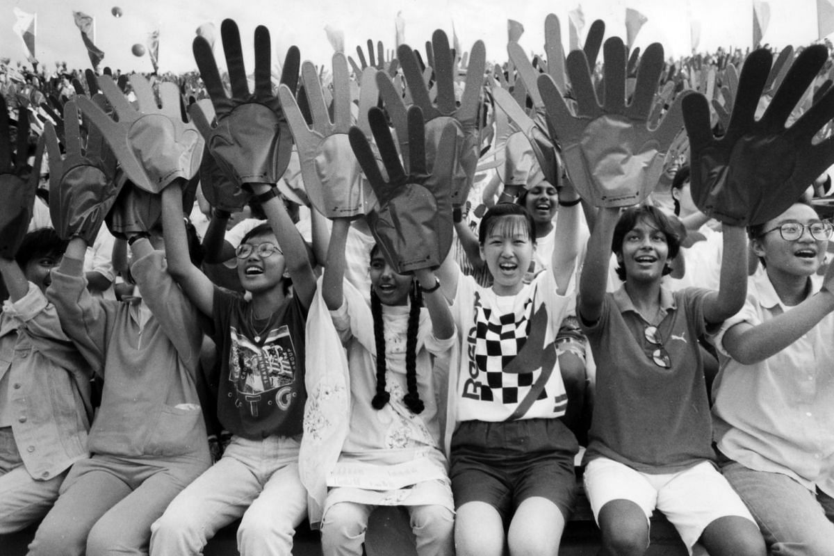 Parade-goers creating a wave of orange and green at the National Stadium in 1989. The outsized PVC gloves were worn by everyone, from toddlers to Cabinet ministers, and symbolised the link between the nation and its people. The giant hands were conce