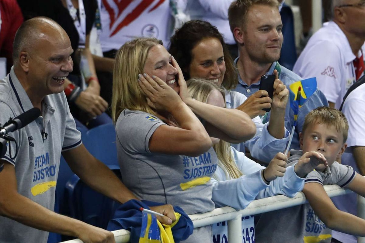 Sweden's Sarah Sjostrom's parents, Goran (left) and Jenny Sjostrom (second from left) celebrate after she broke the World Record and won gold in the Women's 100m Butterfly Final on Aug 7, 2016.