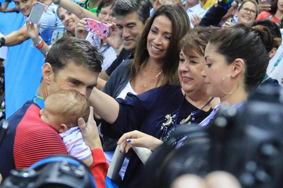 Michael Phelps of USA greets his mother Debbie, fiance Nicole Johnson and their son Boomer after he won the gold medal for men's 200m butterfly on August 9.