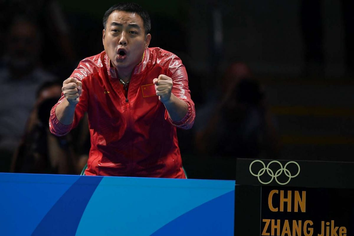 China's Zhang Jike's coach and father Zhang Chuanming cheers his son during a men's singles qualification round table tennis match at the Riocentro venue in Rio de Janeiro on Aug 8, 2016.