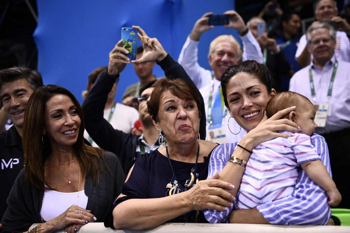 Michael Phelps' mother Deborah (centre) and partner Nicole Johnson (right) cheer after he won the Men's 200m Butterfly Final on Aug 9, 2016.