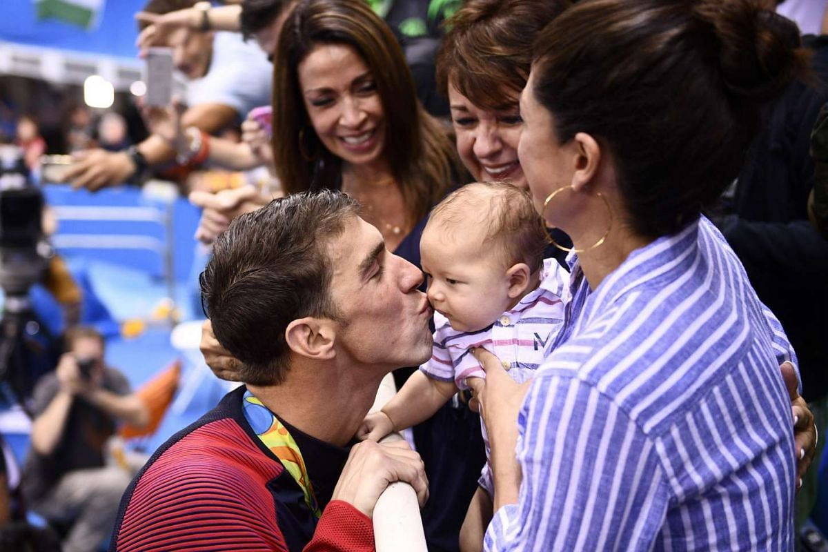Michael Phelps of the US (left) kisses his son Boomer next to his partner Nicole Johnson (right) and mother Deborah (centre) after he won the Men's 200m Butterfly Final on Aug 9, 2016.