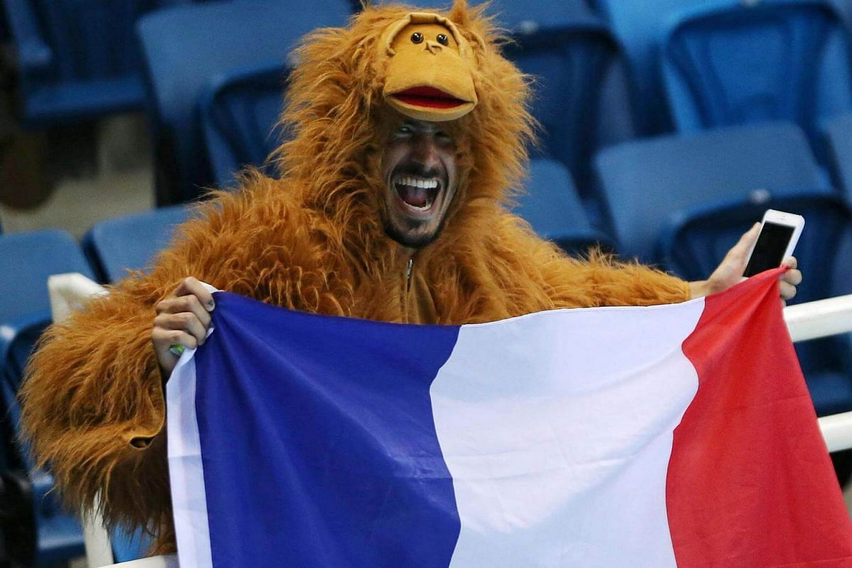 A fan cheers on the France team at the Olympic Aquatics Stadium during the Rio 2016 Olympics.