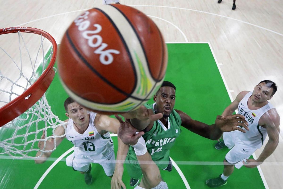 Lithuania's power forward Paulius Jankunas (left) and Nigeria's power forward Alade Aminu (centre) go for a rebound during a Men's round Group B basketball match between Lithuania and Nigeria at the Carioca Arena 1 in Rio de Janeiro on August 9 durin