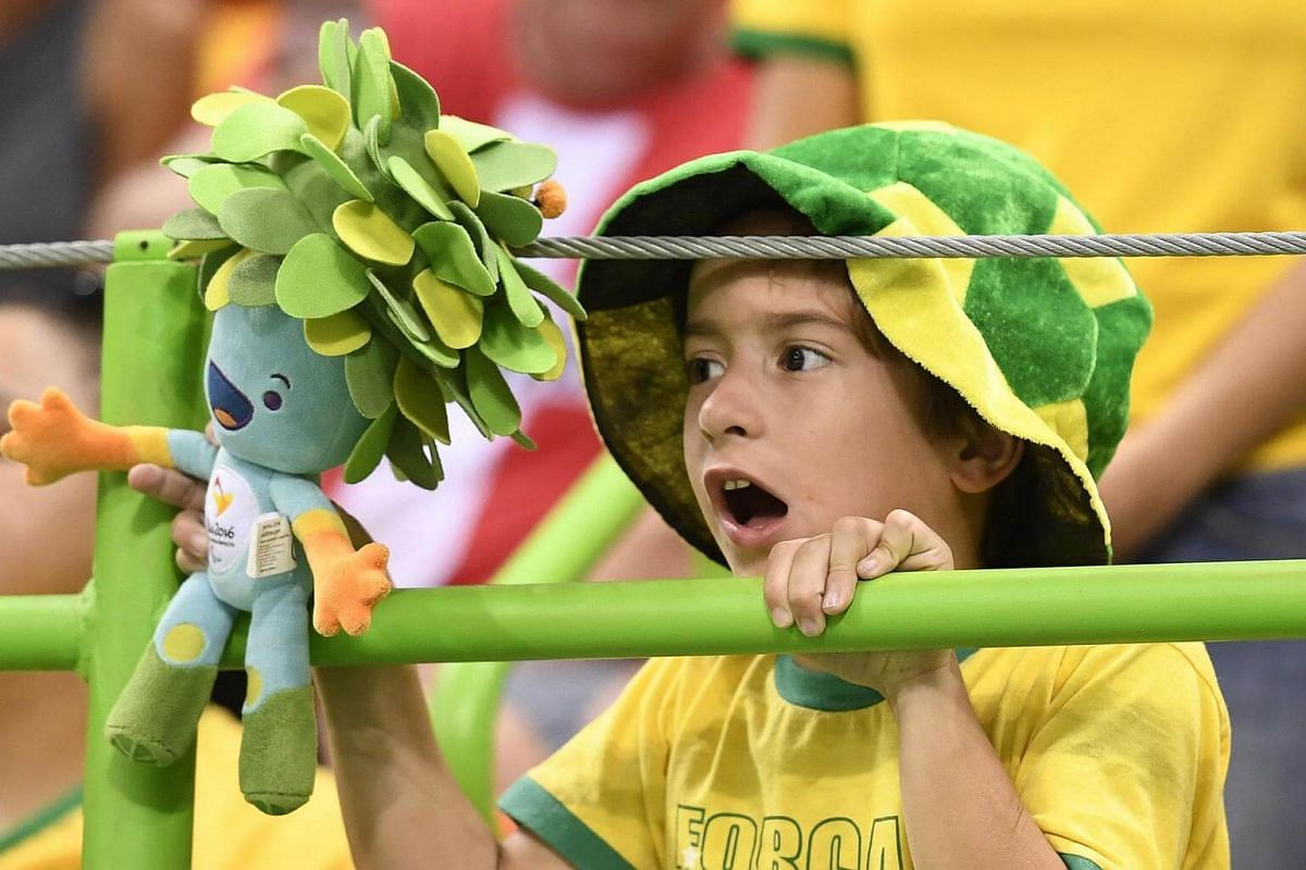 A young Brazilian fan holding the Rio 2016 Paralympic Games mascot Tom cheers his team during the men's preliminaries Group A handball match Brazil vs Slovenia for the Rio 2016 Olympics Games at the Future Arena in Rio on August 9.