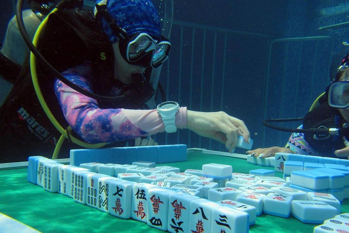 Mahjong enthusiasts playing mahjong under water in a swimming pool at a diving club in the Chinese city of Chongqing on August 7.