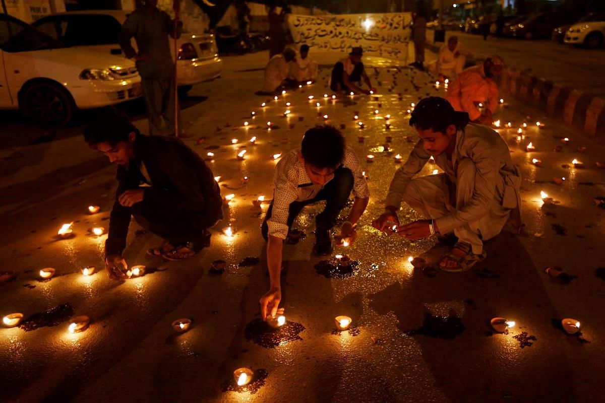 People light oil lamps to honour victims of the blast in Quetta during a vigil in Karachi, Pakistan on August 9.