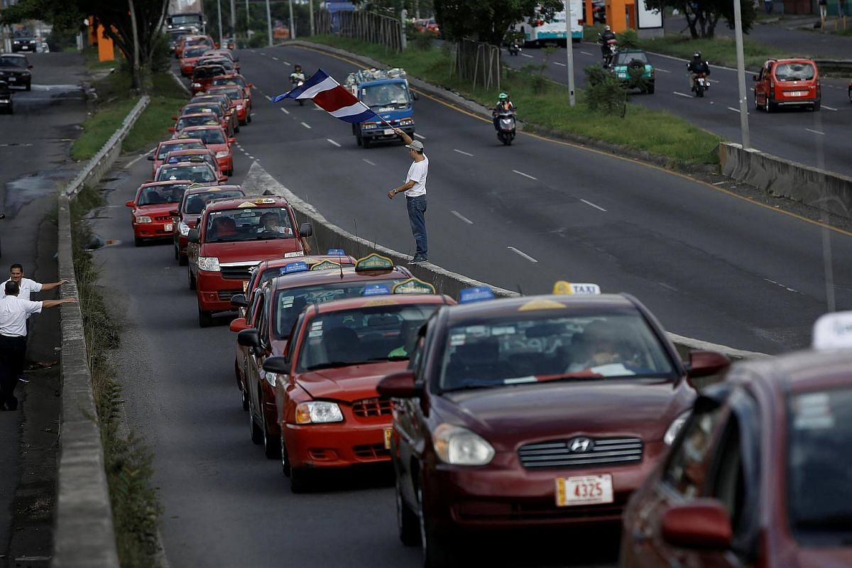 Taxi drivers block a highway during a protest against car-sharing service Uber in San Jose, Costa Rica on August 9.
