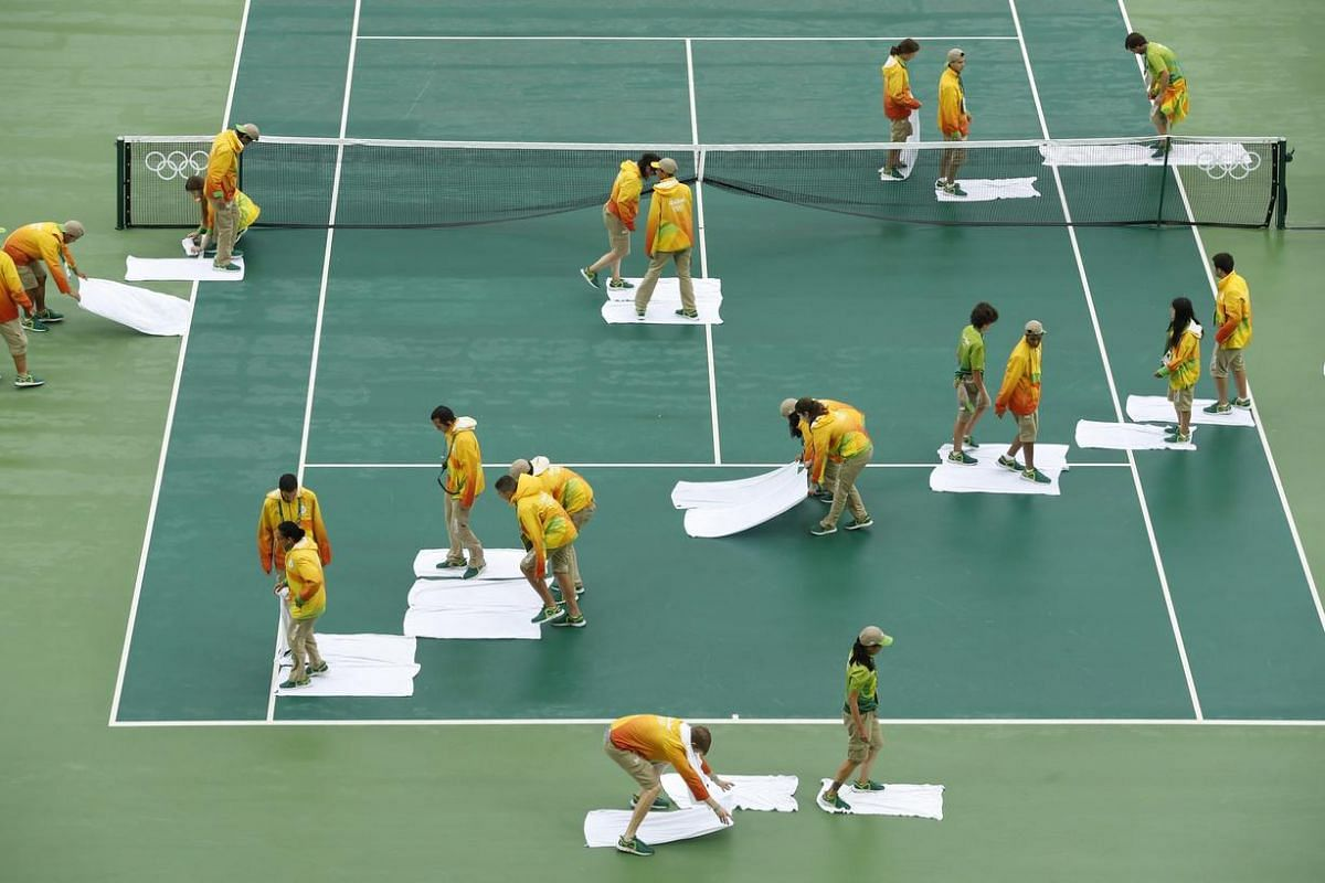 Volunteers use towels to dry off the Center Court during rainy weather at the Olympic Tennis Center on Aug 10.
