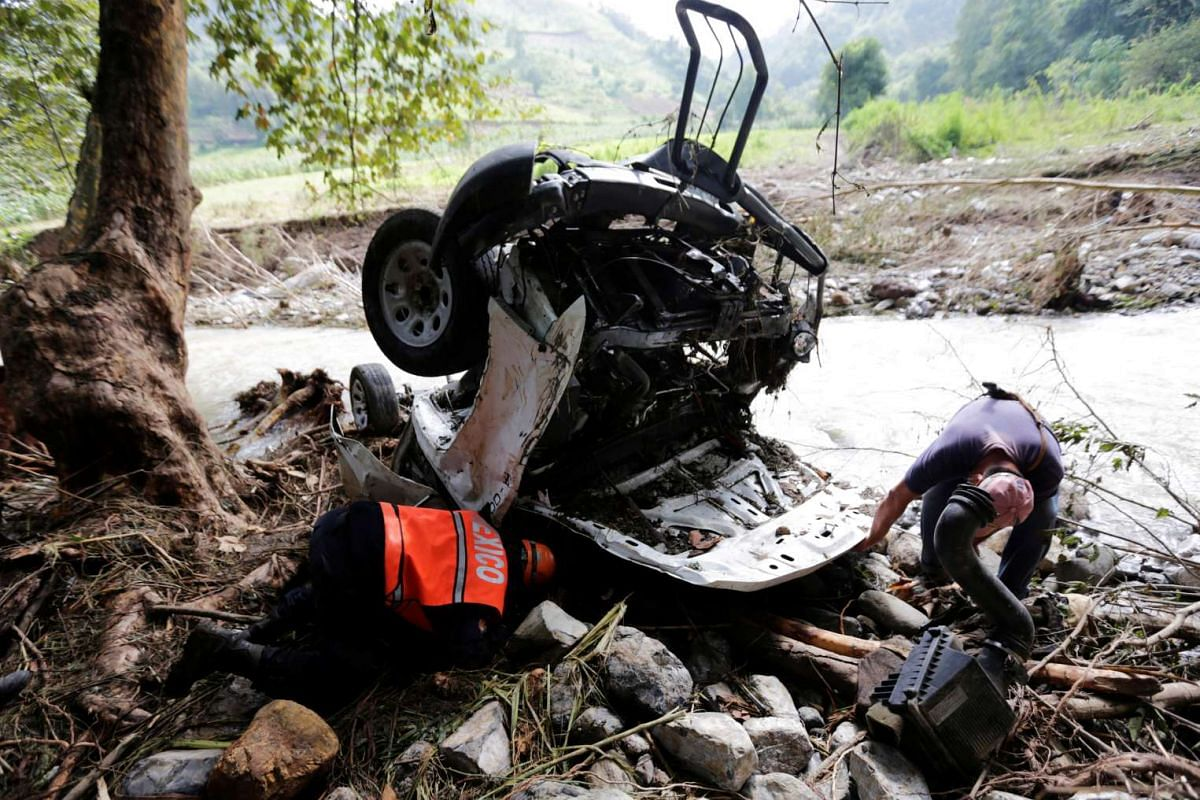 Rescue team members search for victims in a destroyed car after a mudslide in Cuacuila caused by Tropical Storm Earl over the weekend in Puebla, Mexico, on Aug 10, 2016.
