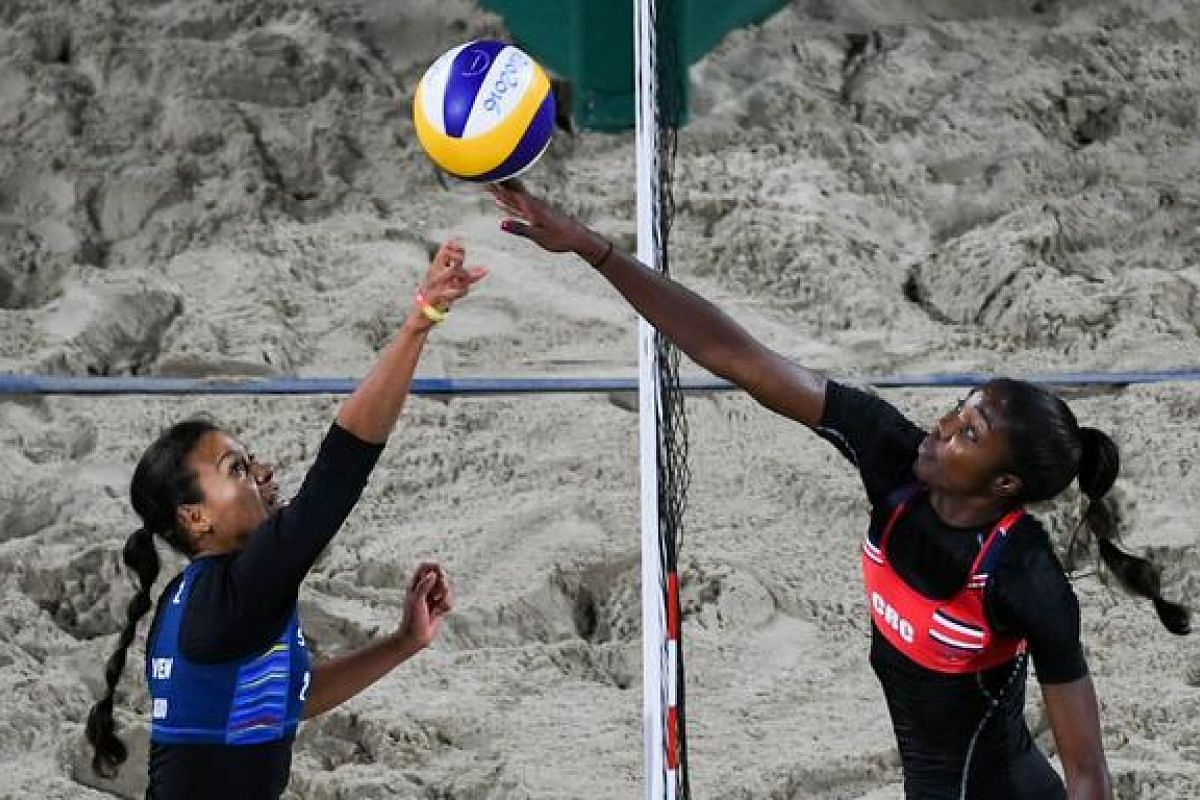 Costa Rica's Karen Cope Charles (right) jumps for the ball in front of Venezuela's Norisbeth Agudo during the women's beach volleyball qualifying match between Costa Rica and Venezuala at the Beach Volley Arena on Aug 10.