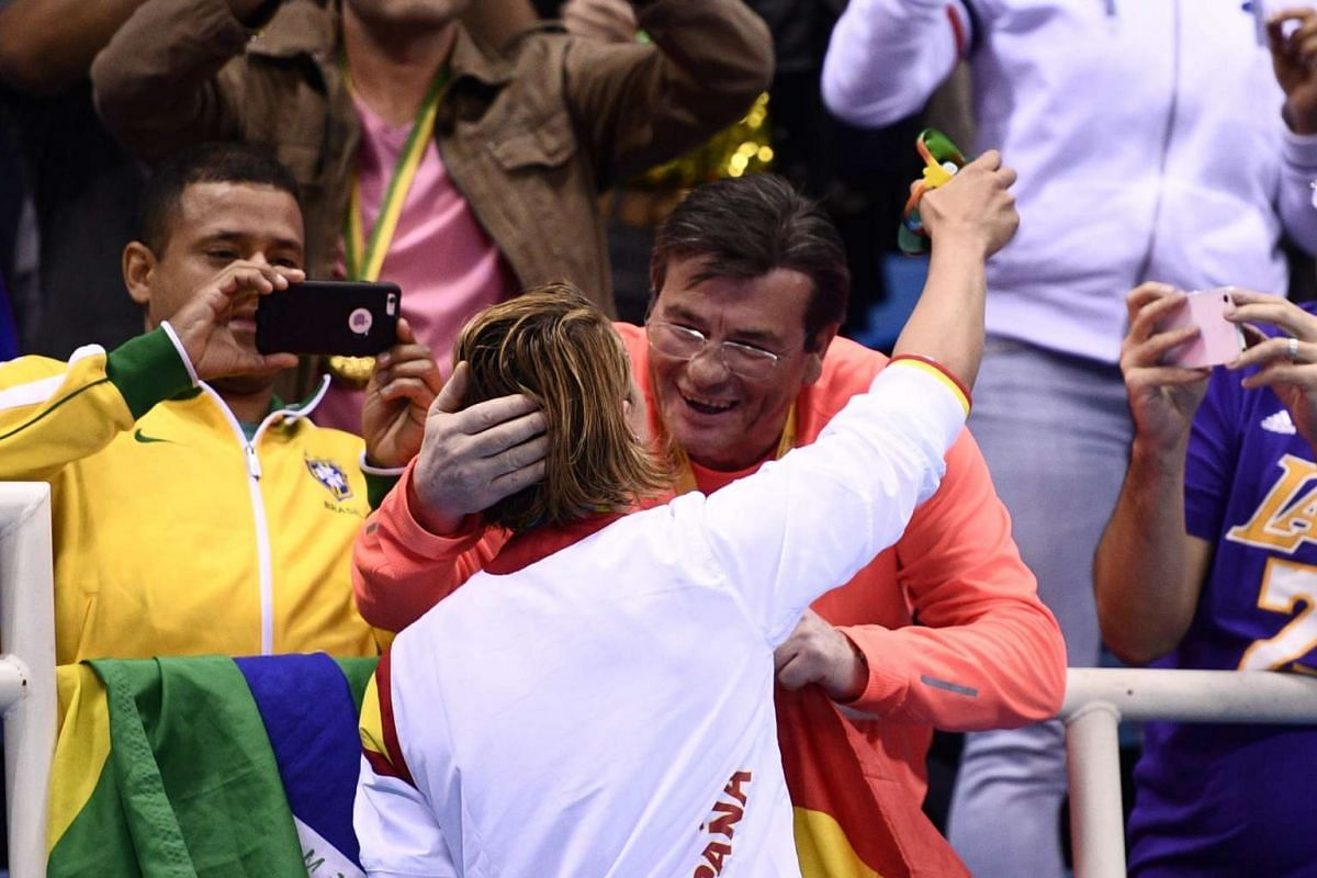 Gold medalist Mireia Belmonte Garcia of Spain (left) hugs her father Jose Belmonte (right) in the stands after the medal ceremony for the women's 200m Butterfly final race of the Rio 2016 Olympic Games at the Olympic Aquatics Stadium on Aug 10, 2016.