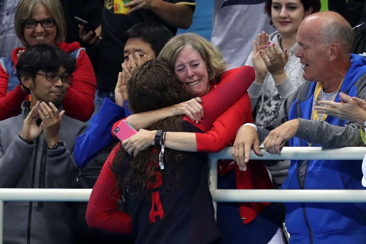 Allison Schmitt of the USA (centre-left) hugs her mother Gail Schmitt (centre-right) in the stands after the medal ceremony for the women's 4x200m Freestyle relay Final race of the Rio 2016 Olympic Games Swimming events at the Olympic Aquatics Stadiu