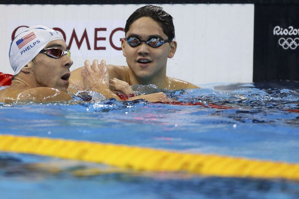 Joseph Schooling of Singapore (left) reacts next to Michael Phelps of the USA during the Men's 100m Butterfly - Heats at the Olympic Aquatics Stadium on Aug 11, 2016.