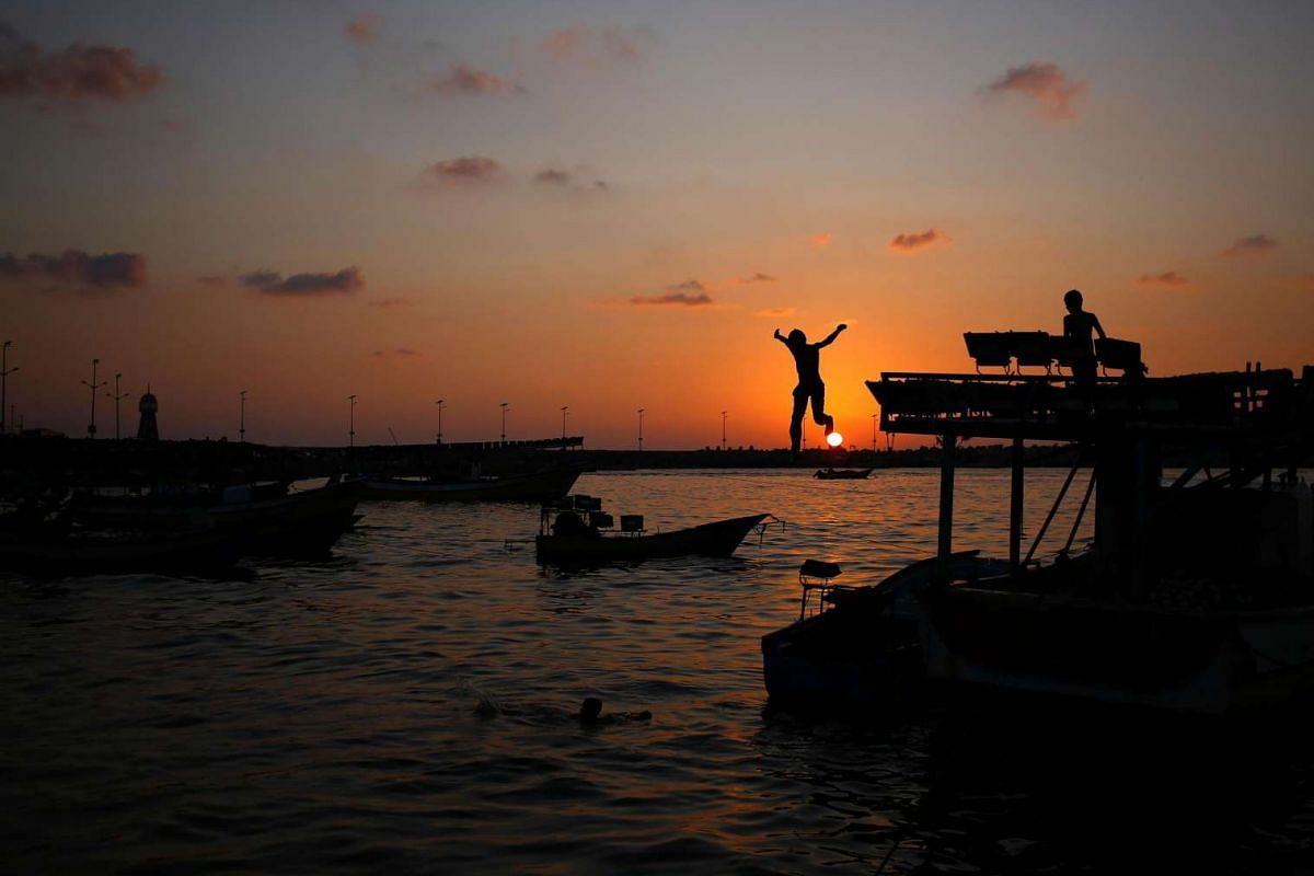 A boy jumps into the sea at sunset in Gaza City on Aug 11.