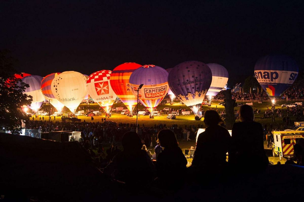 "Members of the public watch tethered hot air balloons perform a ""Nightglow"" on the opening day of the Bristol International Balloon Fiesta in Bristol on Aug 11."