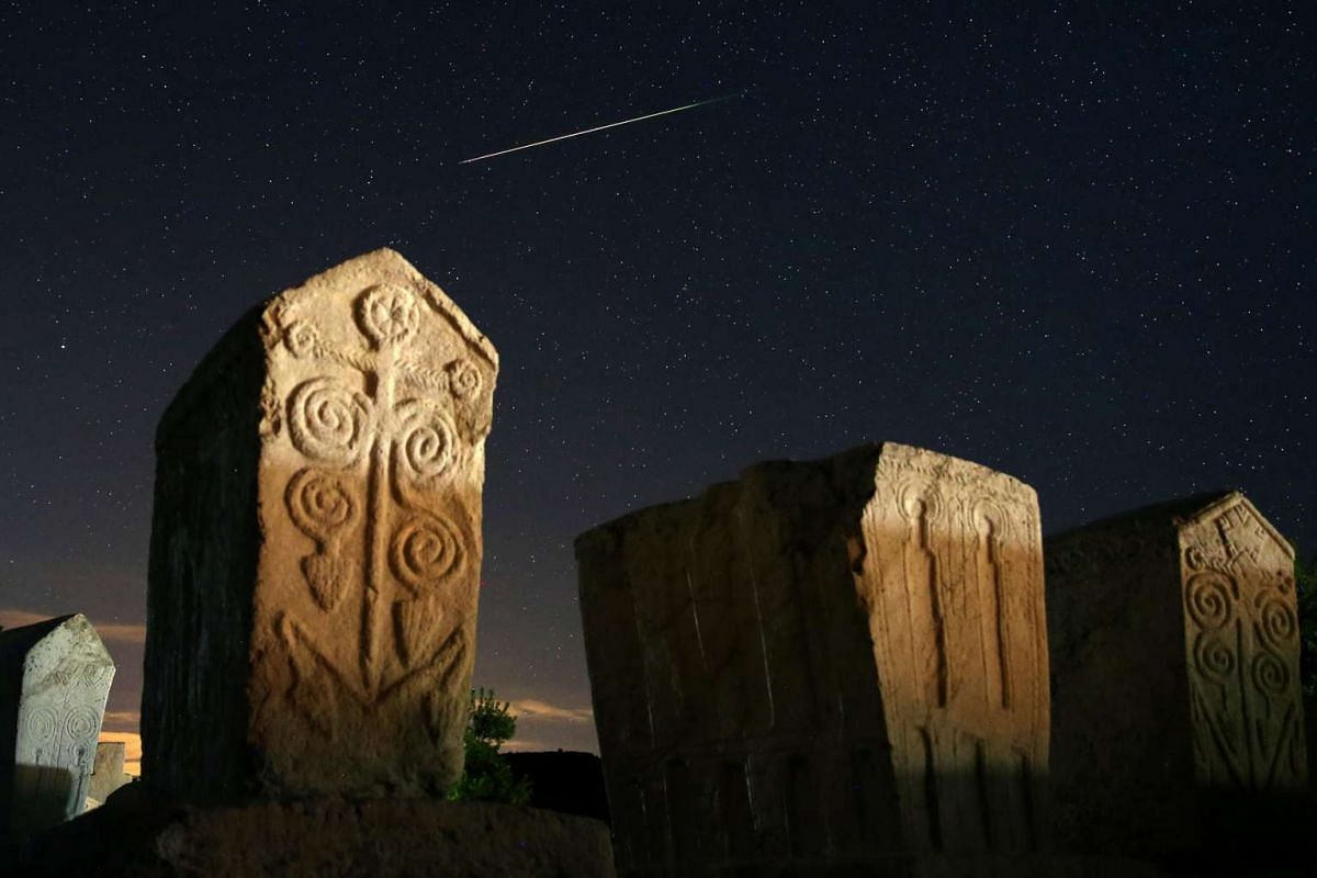 A meteor streaks past stars in the night sky above medieval tombstones in Radmilje, near Stolac, Bosnia and Herzegovina, on Aug 12.