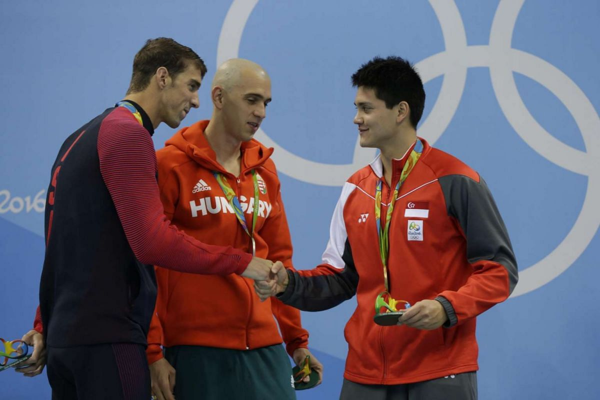 Joseph Schooling of Singapore congratulated by Michael Phelps on the podium after winning the Rio 2016 Olympic Games men's 100m butterfly final at the Olympic Aquatics Stadium in Rio de Janeiro, Brazil, on Aug 12, 2016.