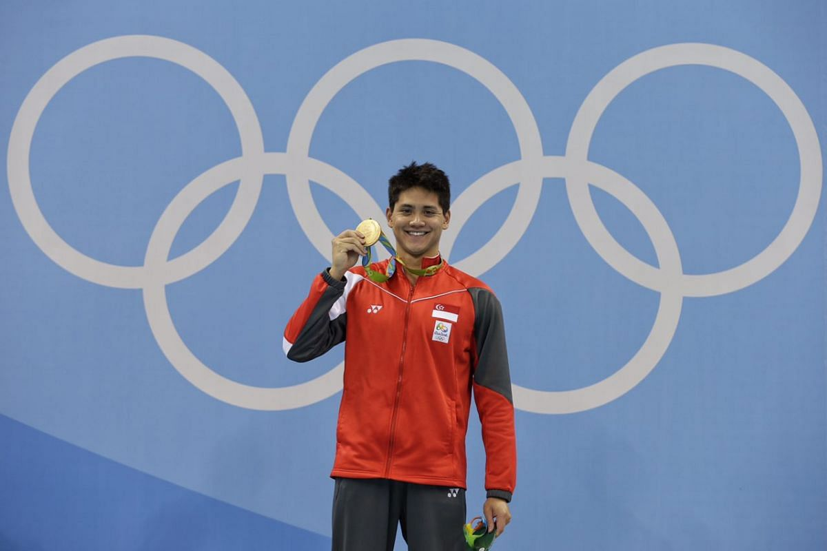 Joseph Schooling holding his medal on the podium after winning gold for the men's 100m butterfly final on Aug 12.