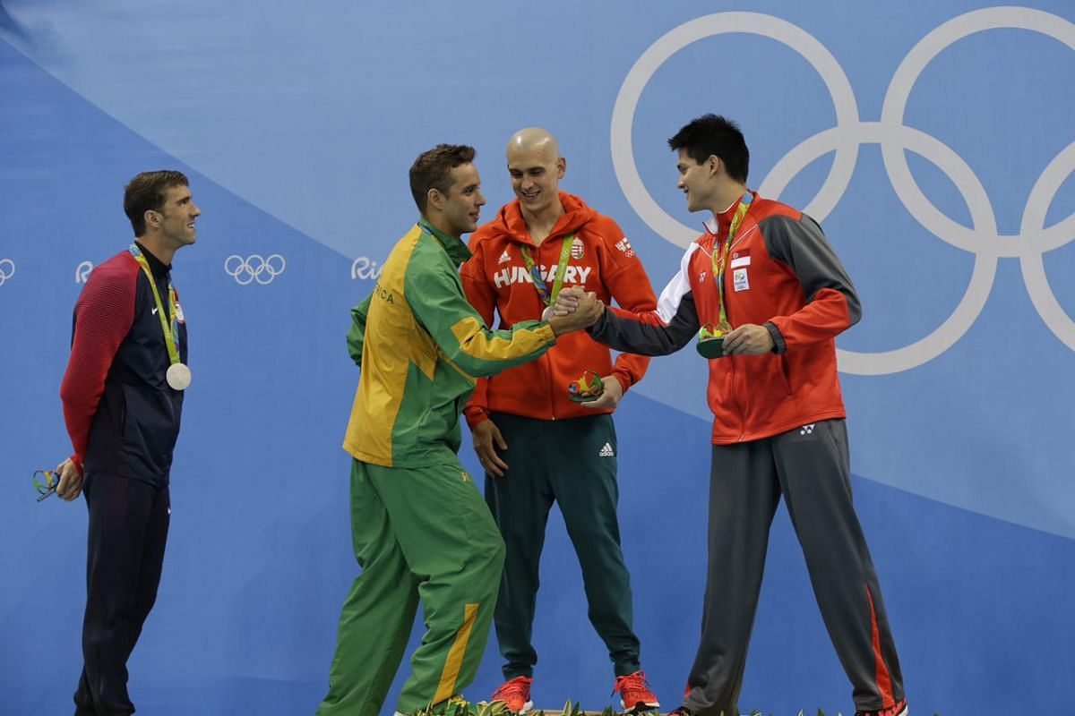 Joseph Schooling being congratulated by the silver medalists at the victory ceremony on Aug 12.