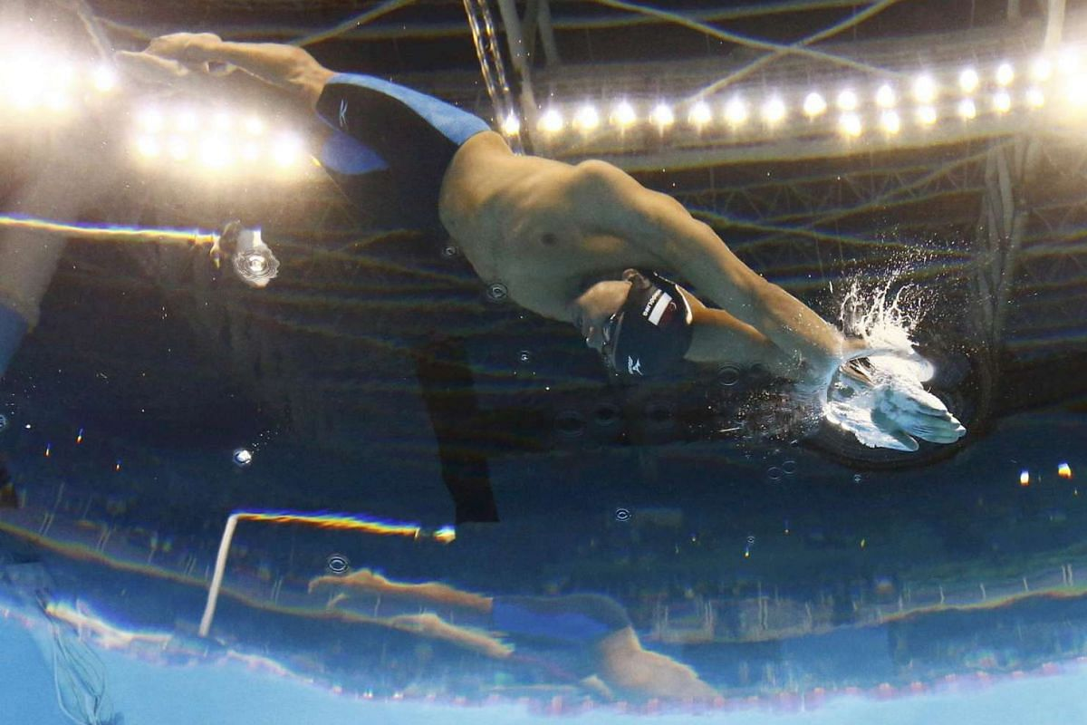 Joseph Schooling (right) dives during the men's 100m butterfly final on Aug 12.