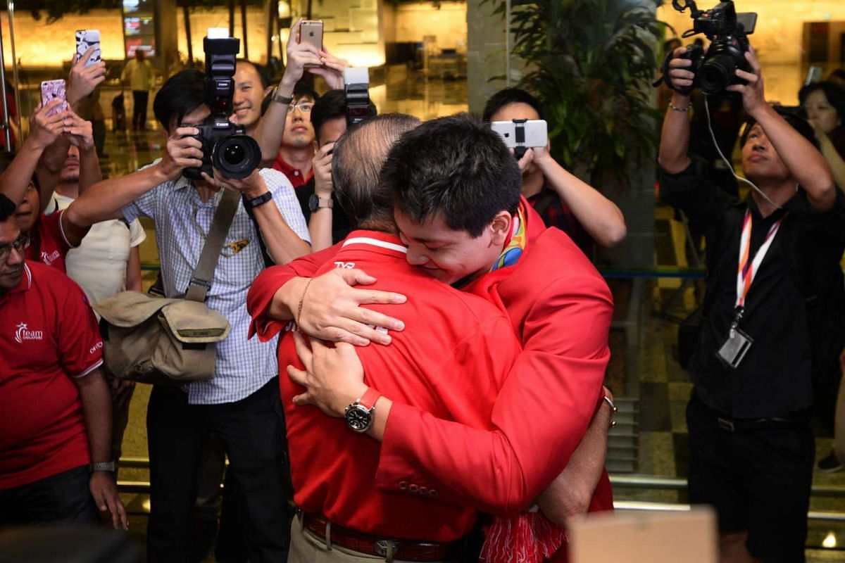 Joseph Schooling, Singapore's Olympic gold medalist and hero, hugs his father, Colin, after returning to Singapore on August 15, 2016. PHOTO: STRAITS TIMES/Mark Cheong