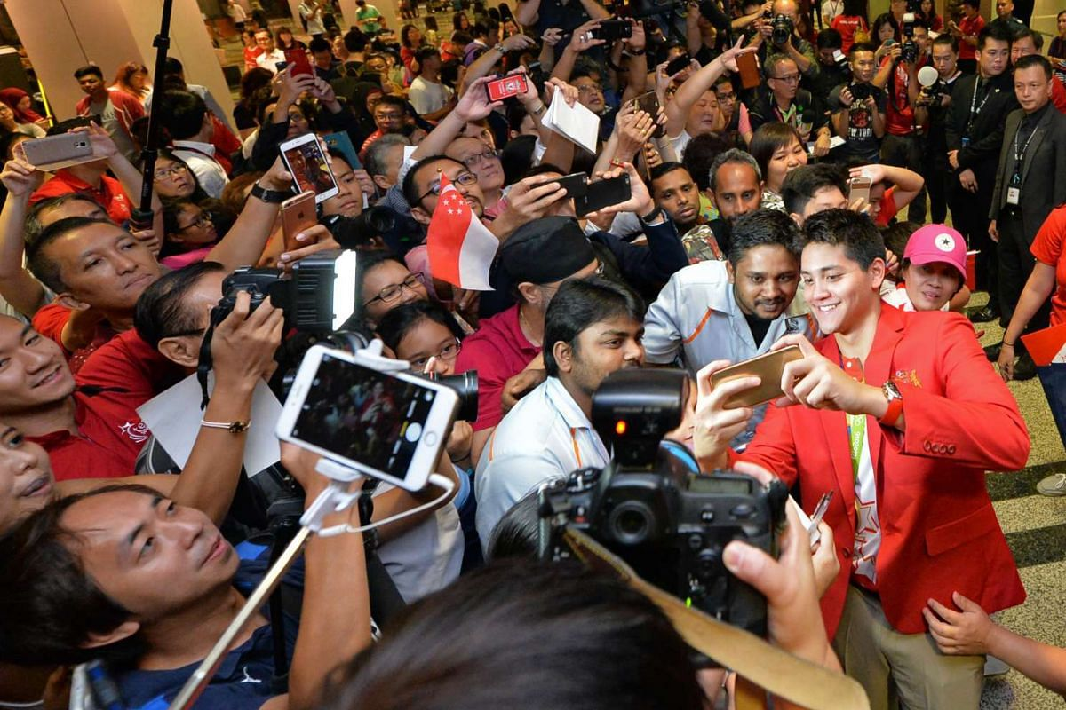Joseph Schooling, Singapore's Olympic gold medalist and hero, takes a selfie with fans after returning to Singapore on August 15, 2016. PHOTO: STRAITS TIMES/Desmond Foo