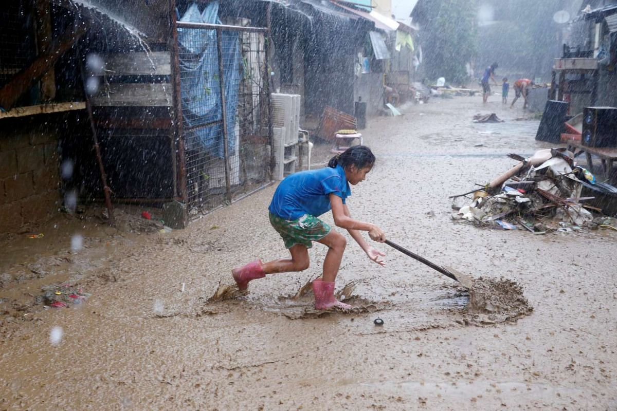 A resident removes mud on a street brought by monsoon rains in San Mateo, Rizal, Philippines, August 14, 2016. PHOTO: REUTERS