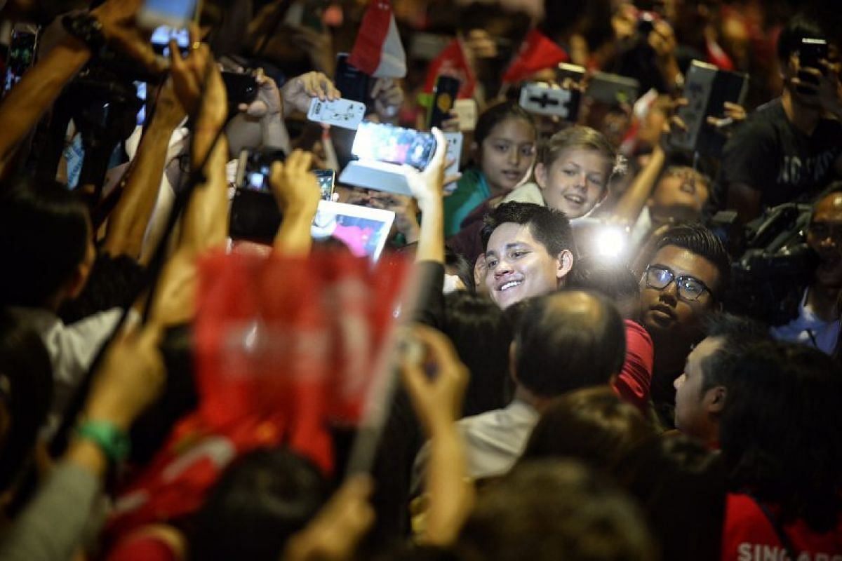 Joseph Schooling is the centre of attention of adoring fans as he moves through the crowd.