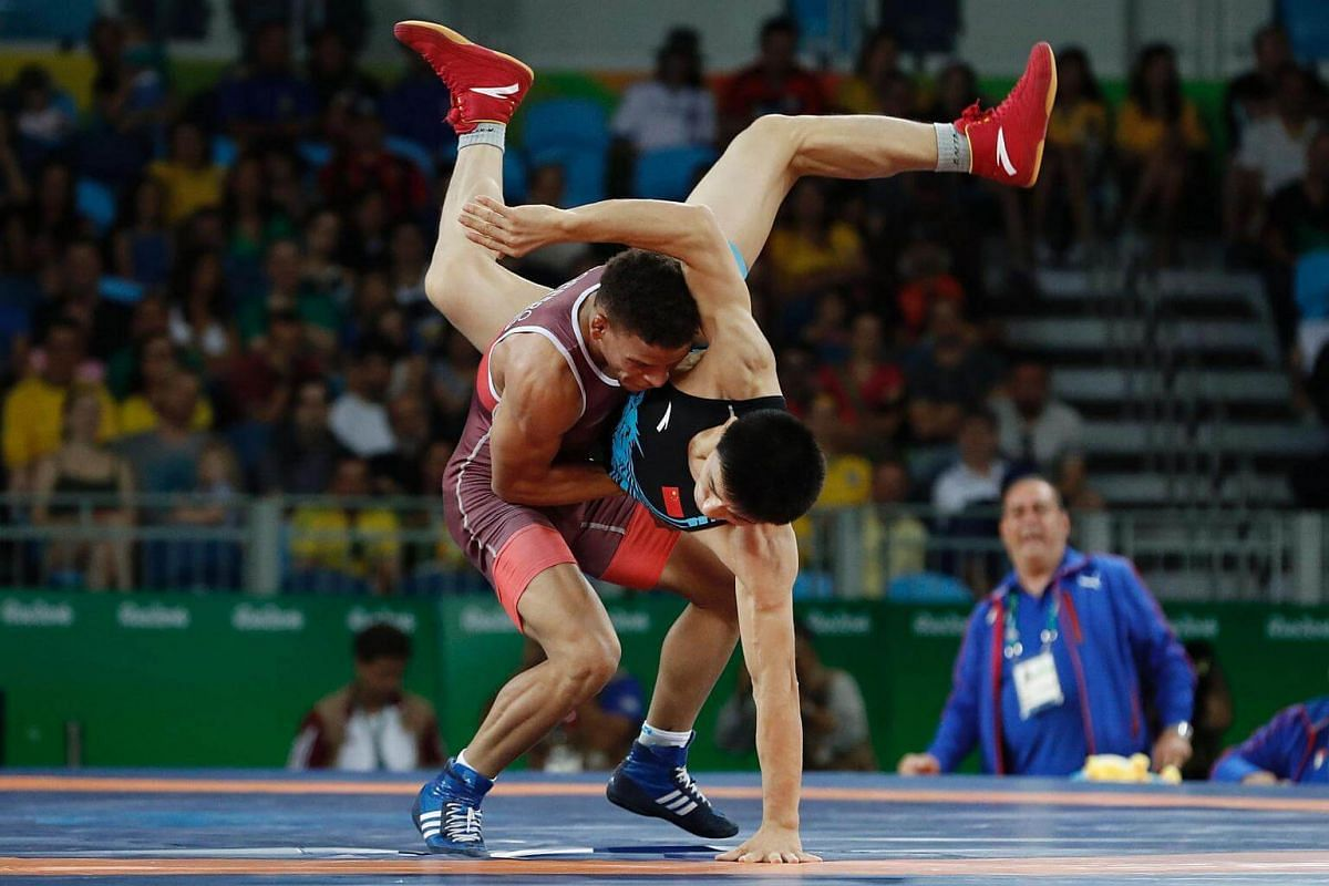 Cuba's Ismael Borrero Molina (red) wrestles with China's Wang Lumin in their men's 59kg greco-roman quarter-final match on Aug 14.
