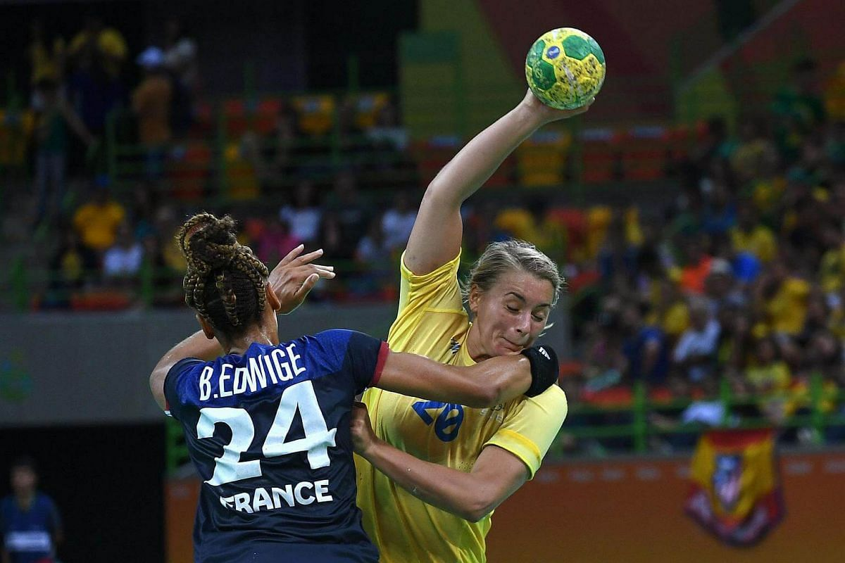 Sweden's centre back Isabelle Gullden (right) vies with France's pivot Beatrice Edwige during the women's preliminaries Group B handball match Sweden vs France v Brazil on Aug 14.