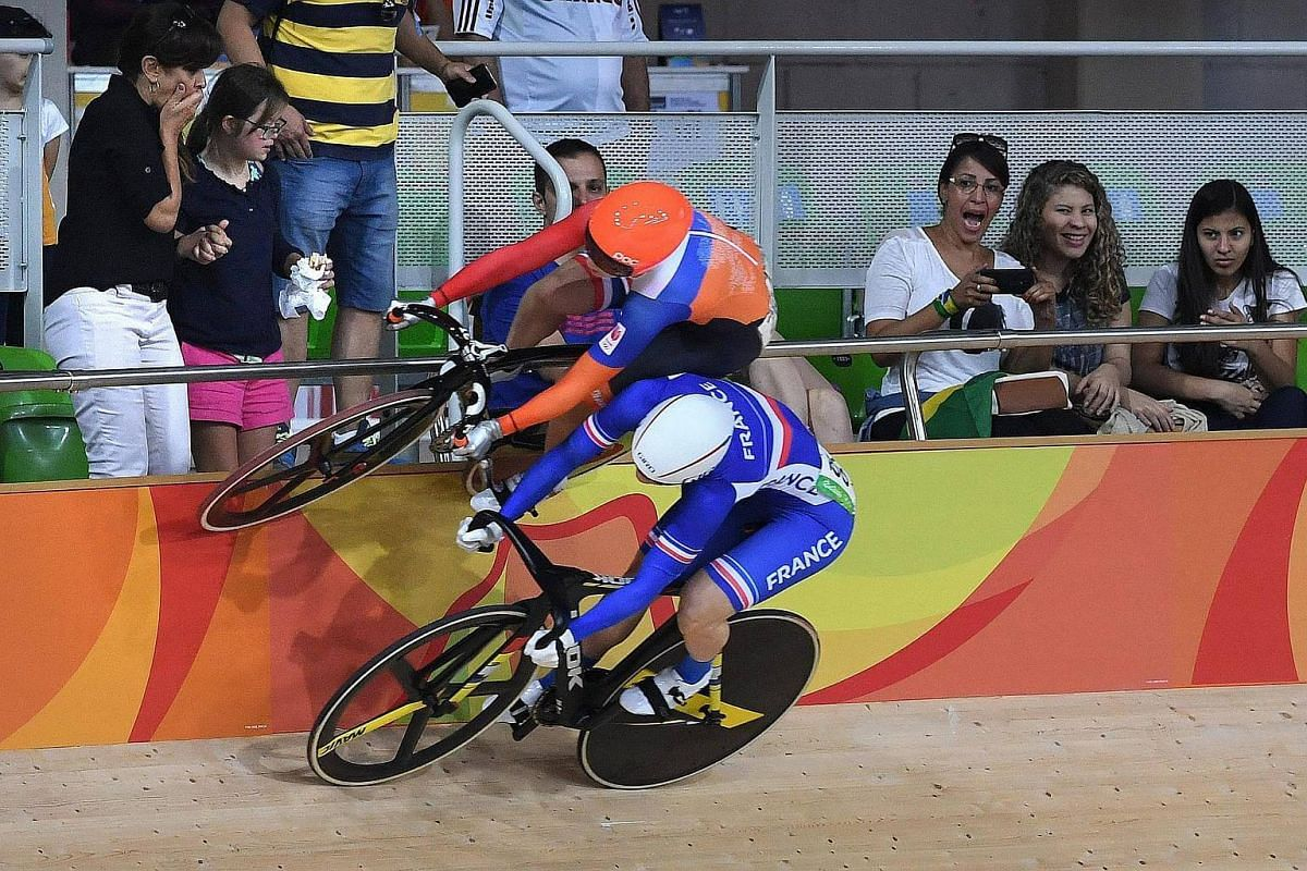 Lauren van Risen of Netherlands (left) rides on the barrier wall with Virginie Cueff of France after evading a crash during heat two of the first round of the women's keirin race on Aug 14.
