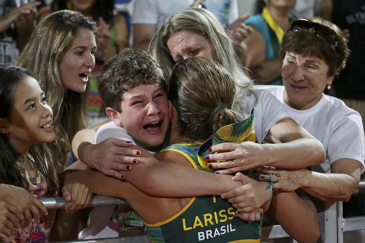 Larissa of Brazil is embraced by her nephew Enzo Buaruqe, nine, after defeating Switzerland on Aug 14.