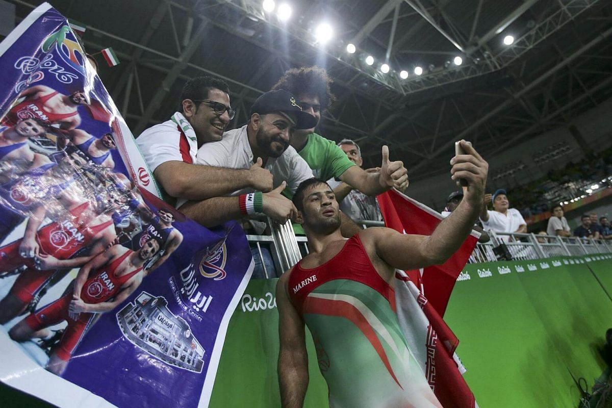 Saeid Mourad Abdvali of Iran takes a selfie with supporters as he celebrates winning the bronze medal.