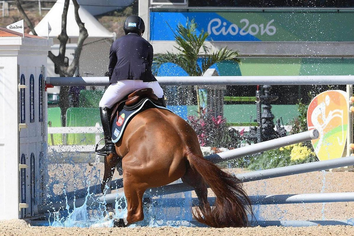 Brazil's Eduardo Menezes on Quintol hits an obstacle during the equestrian show jumping first qualifier event of the 2016 Rio Olympic Games on Aug 14.