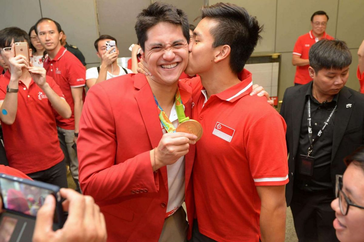 Joseph Schooling receives a welcome kiss from his buddy Teo Zhen Ren.