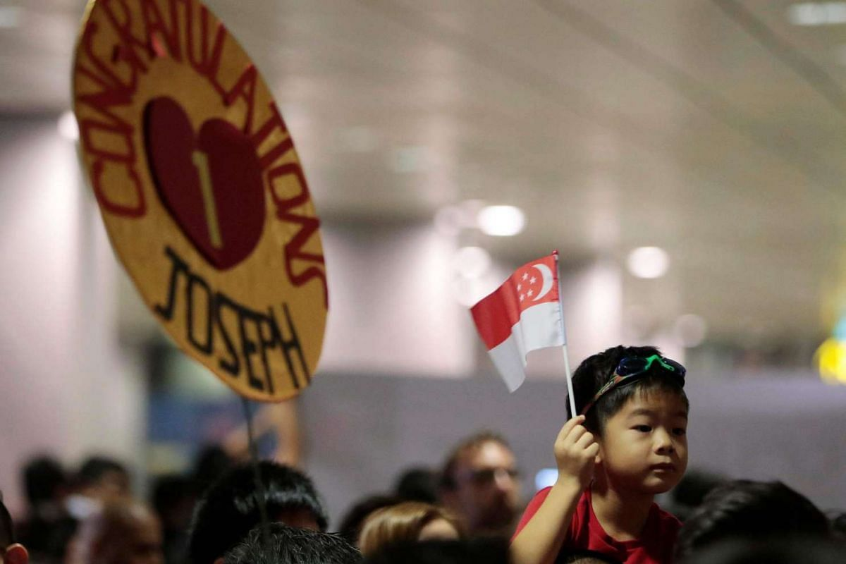 A young boy with a Singapore national flag while held up above a crowd awaiting the arrival of Olympic gold medalist Joseph Schooling of Singapore in the arrival hall of the Changi Airport on Aug 15.