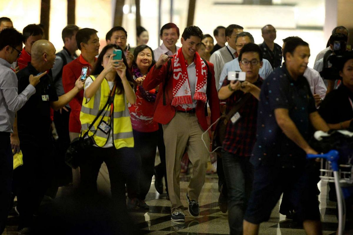 Joseph Schooling, Singapore's Olympic gold medallist, raises his fists at the baggage collection area after returning to Singapore on Aug 15.