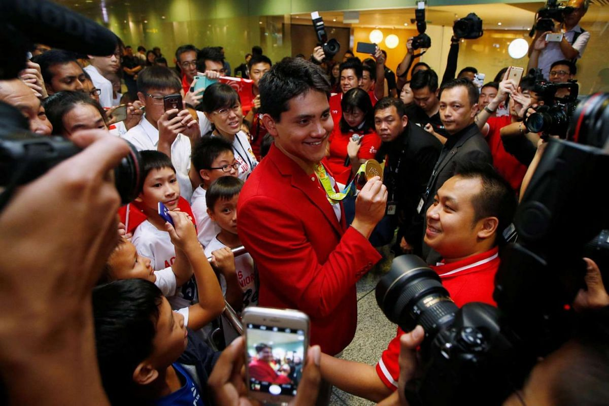 Singapore Olympic gold medallist swimmer Joseph Schooling shows his medal to fans during a homecoming ceremony at Singapore's Changi Airport on Aug 15.