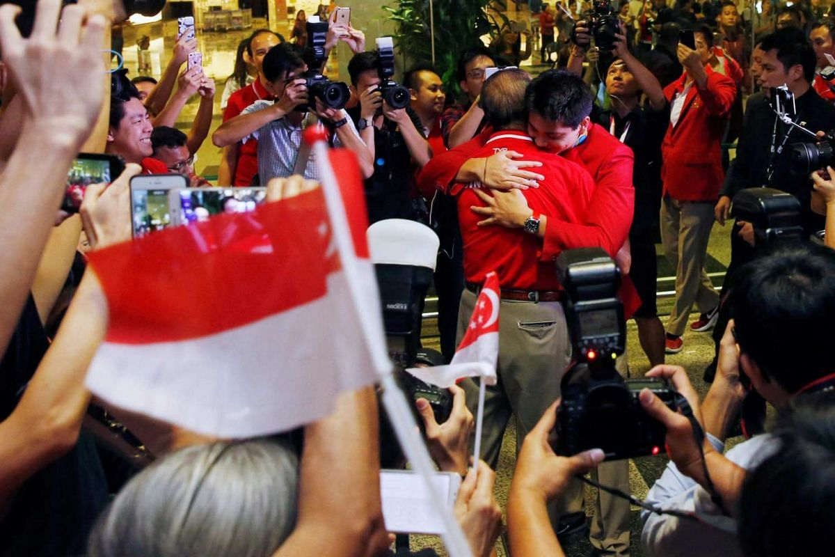 Singapore Olympic gold medallist swimmer Joseph Schooling hugs his father Colin Schooling during a homecoming ceremony at Singapore's Changi Airport on Aug 15.