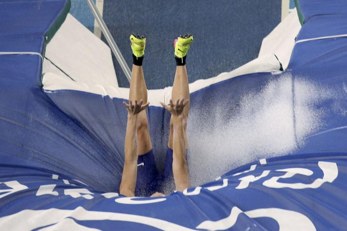 Water splashes up as Sam Kendricks of US lands after a jump in the Men's Pole Vault Final.