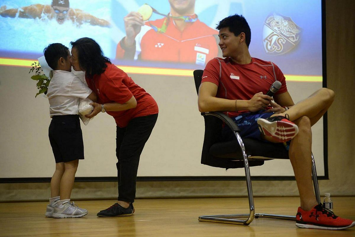 Mrs May Schooling gives nine-year-old ACS Junior student Darion Pang a peck on his cheek after receiving a bouquet of flowers from him as a token of appreciation from the school as Joseph Schooling looks on at ACS Junior on August 15.
