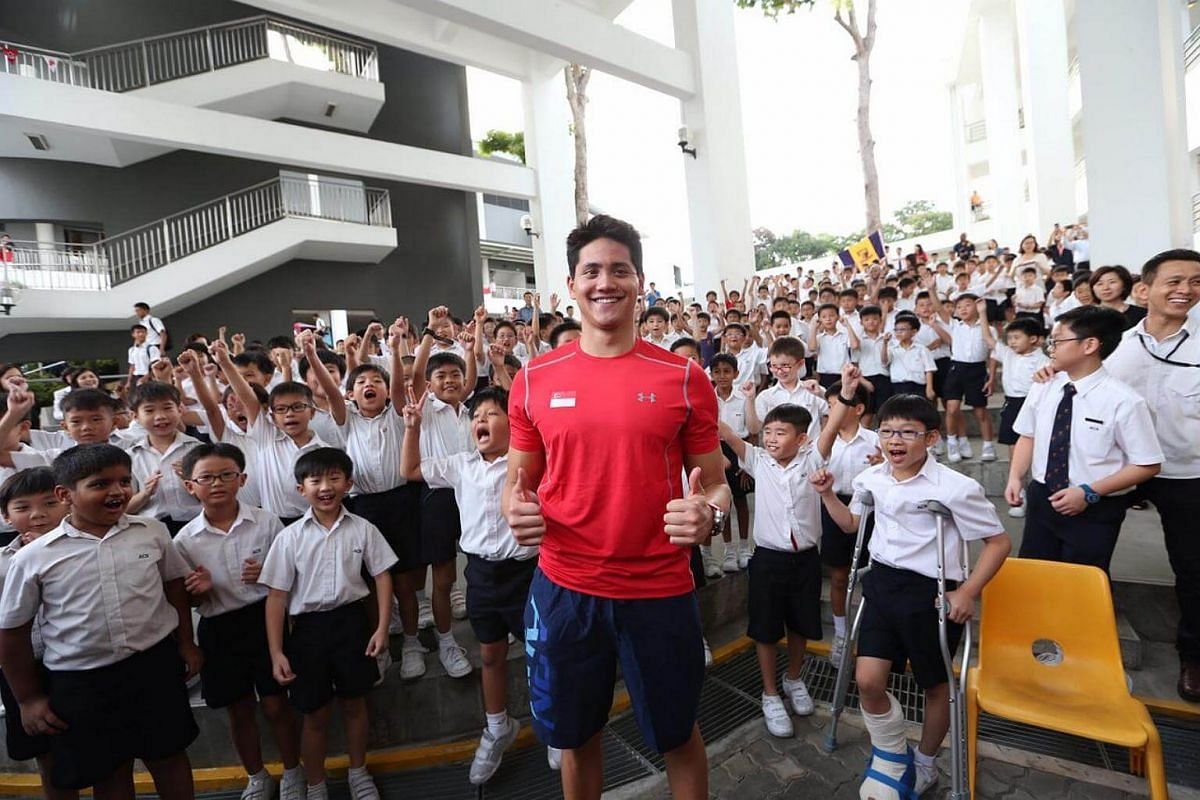 Joseph Schooling posing with excited students from ACS Junior.
