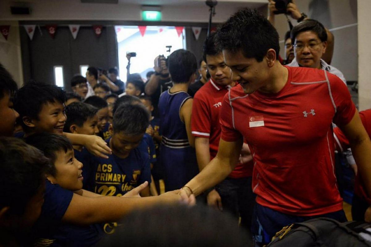 Joseph Schooling shaking hands with lucky students.