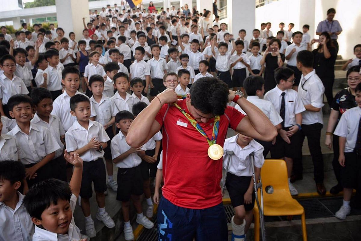 Joseph Schooling puts on his Olympic gold medal as ACS Junior students look on.