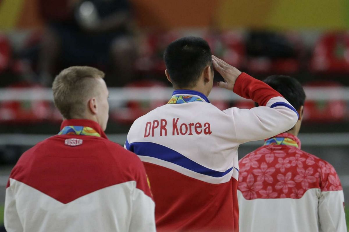 Ri Se Gwang (centre) of North Korea saluting his national flag during the anthem after winning gold in the artistic gymnastics men's vault at the Rio Olympic Arena in Rio de Janeiro on August 15.